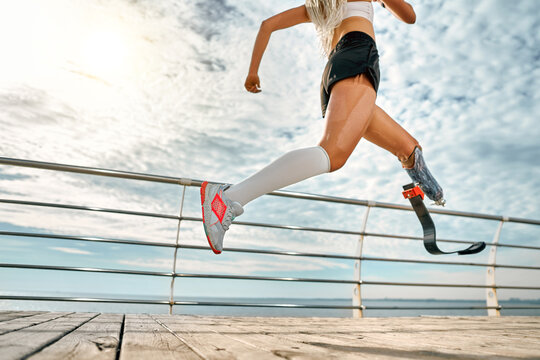 Cropped side view of young amazing disabled sports woman running on the bridge outdoors.