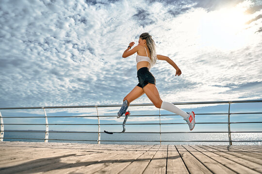 Full length portrait of a confident young disabled sportswoman running fast on the bridge near the sea.
