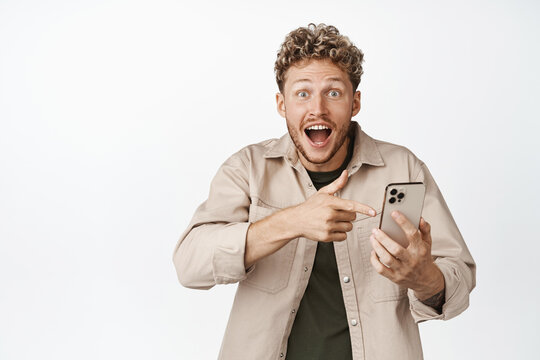 Amazed blond guy pointing finger at mobile phone screen, reacting amazed at something awesome on smartphone, standing against white background