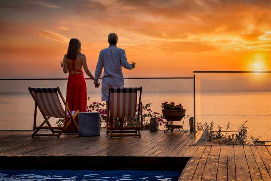 A romantic couple on summer vacation enjos the sunset over the mediterranean sea by the pool with a glass of wine