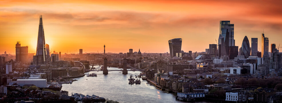 Golden sunset behind the modern skyline of London, with Tower Bridge, Thames river and City skyscrapers