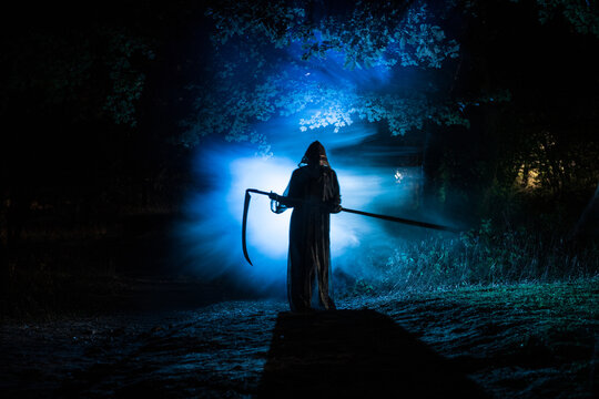 Death with a scythe in the dark misty forest. Woman horror ghost holding reaper in forest