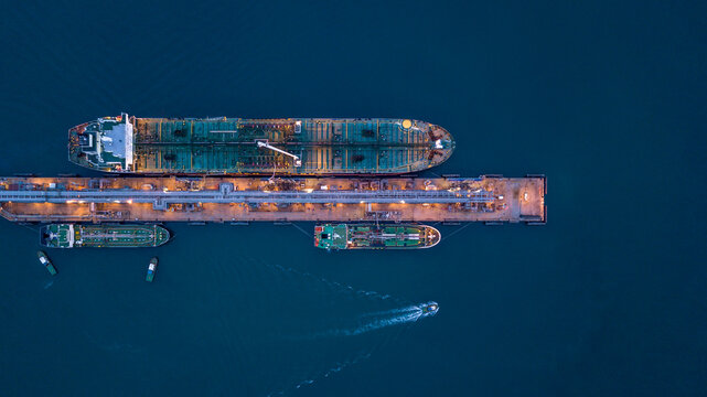 Aerial view oil ship tanker at terminal sea port, Large crude oil tanker unloading at port, Business import export oil and gas petrochemical with tanker ship transportation oil from dock refinery.