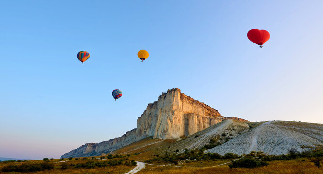 Landscape with colorful balloons at sunrise.