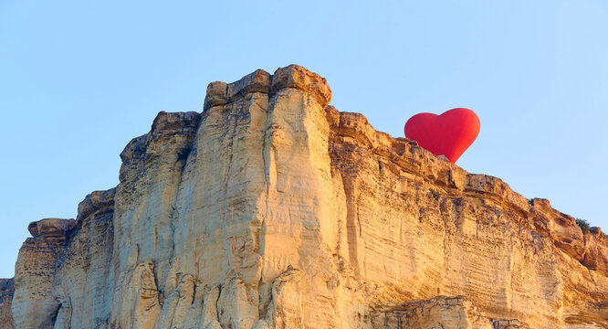 White rock with heart shaped balloon in sunlight.