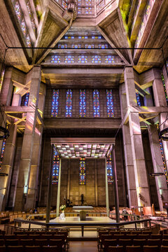 Le Havre, France - June 7, 2021: Side view of the altar in the center of St Joseph church, built in 1957 after french architect Auguste Perret and illuminated through stained glass by Marguerite Hure.