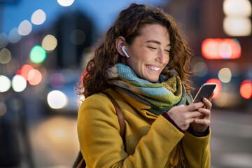 Obraz Woman on street using phone at evening - fototapety do salonu