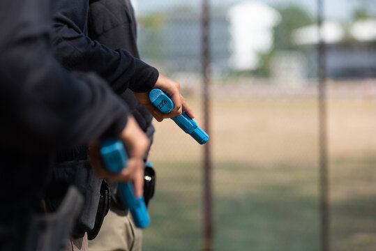 Police practice using blue rubber firearms in the lawn.