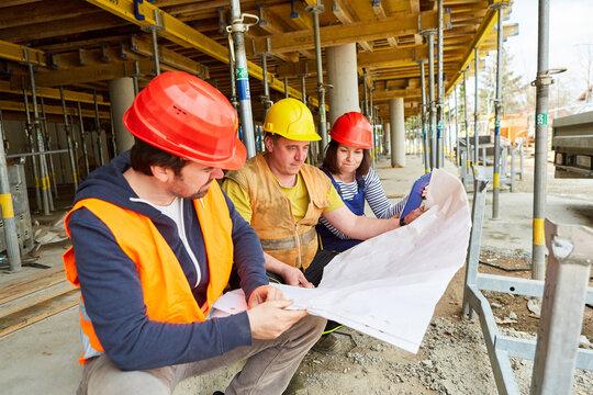 Handwerker und Architekten mit Bauzeichnung bei Hausbau