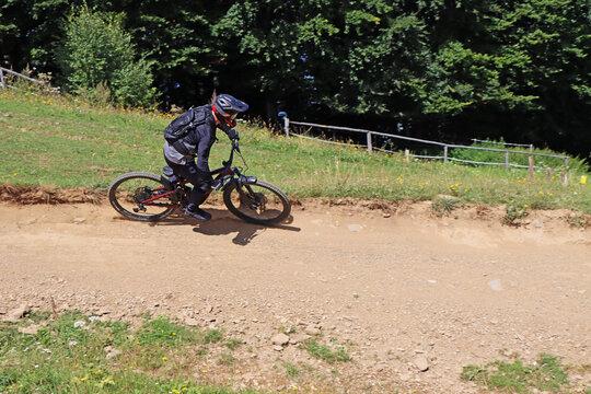 Man on mountain bike rides mountain trail.