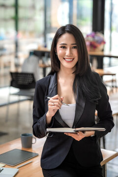 Beautiful young Asian businesswoman holding a pen with a work concept notebook. Looking at the camera.