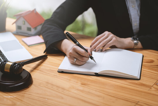 Close-up of businesswoman judge hand holding a note-taking pen in the courtroom real estate law concept, mallet, laptop placed at the table