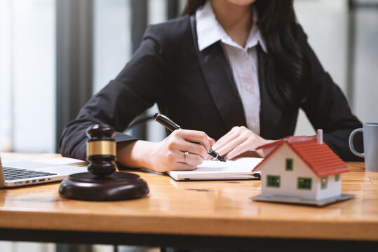 Close-up of woman lawyer hand holding a pen to taking notes real estate ideas sample house mallet empty  at the office.