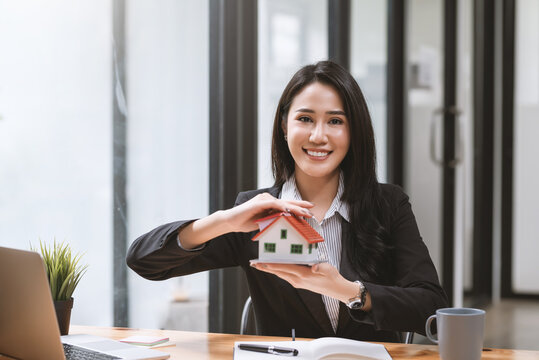 Young Asian businesswoman real estate agent holding house samples mortgage. Looking at the camera.