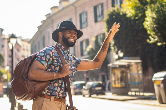 Trendy black tourist with backpack catching taxi in city
