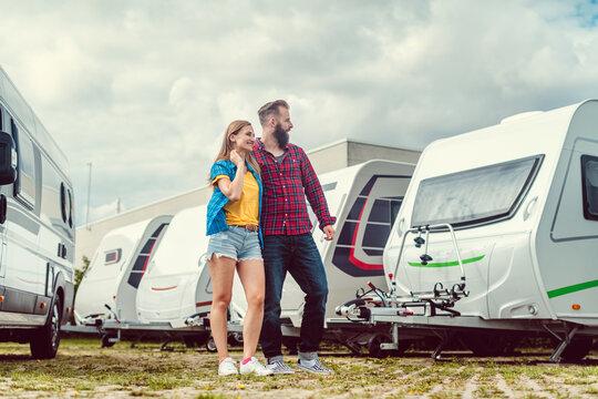 Woman and man choosing camper van to rent or buy on yard of dealer