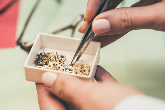 Watchmaker sorting cogwheels in little container with pincers searching for the right spare part