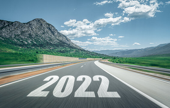 2022 New Year road trip travel and future vision concept . Mountain landscape with highway road leading forward to happy new year celebration in the beginning of 2022 for successful start .