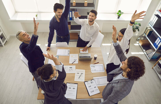 Excited diverse team celebrating corporate business success with raised hands standing around office desk overhead view. Coworker congratulating each other with achievement and good project result