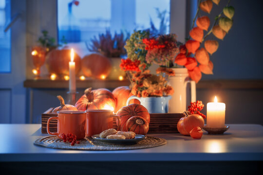 two orange cups  of tea and autumn decor with pumpkins, flowers and burning candles on table
