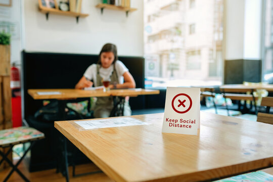Coffee shop table with do not use sign to keep social distance with girl in the background having a drink