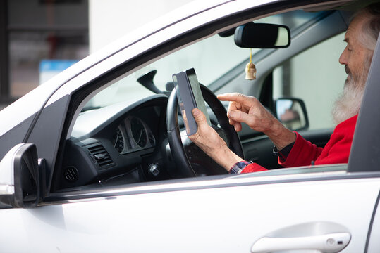 Bearded senior man holding phone and texting while sitting in car a parking lot