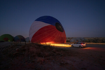 A car parked in front of a hot air balloon with headlights on during night, preparation of a flight in Goreme national park in Cappadocia, Turkey