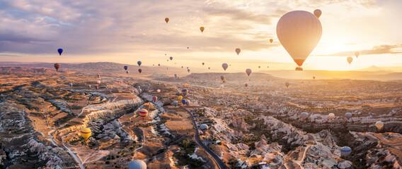Fototapeta Hot air balloons flying above Göreme, Cappadocia (Kapadokya) Anatolia, Turkey at sunrise. Panoramic view of villages and fairy chimneys. Popular touristic destination for summer vacation holidays obraz