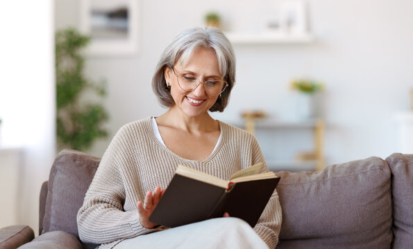 Beautiful happy senior woman with grey hair in eyeglasses reading book and smiling