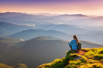 Young woman with backpack sitting on the mountain peak and beautiful mountains in fog at sunset in autumn. Landscape with sporty girl, green grass, forest, hills, sky, sunbeams in fall. Travel. Nature