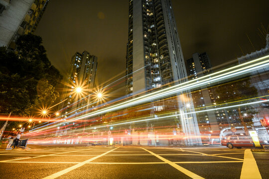 Light Trails On City Street By Buildings Against Sky At Night In Hong Kong