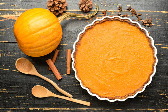 Composition with delicious pumpkin pie on black wooden background