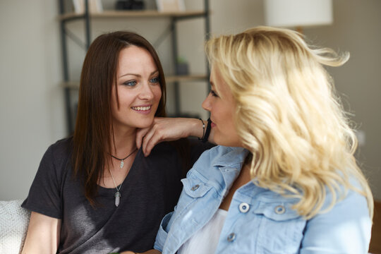 Closeup of two young women flirting in the living room