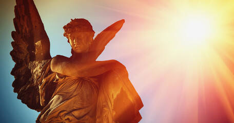 Ancient statue of golden angel illuminated by sunlight