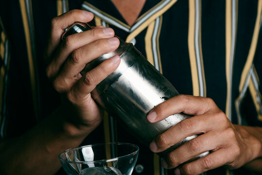 young man prepares a cocktail in a metal shaker