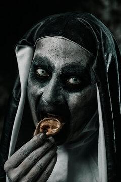 evil nun eating a human ear