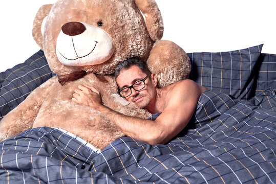 A young man sleeps in an embrace with a teddy bear in bed.