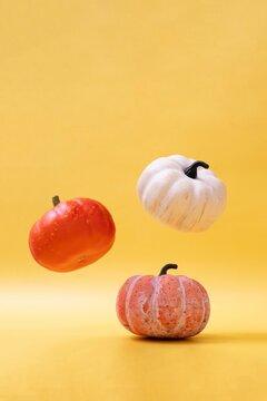 Three pumpkins on warm background. Levitation autumn, halloween concept. Horizontal image.