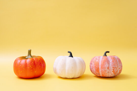 three pumpkins on warm background. Template for autumn and halloween concepts. Copy space.