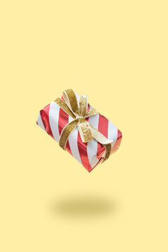 Flying christmas gift box, with golden bow, on warm background. Holiday gift concept.