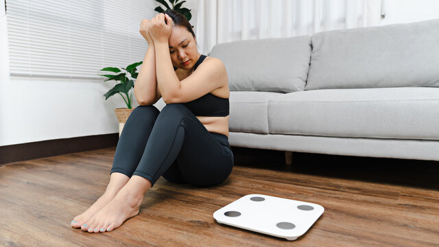 Asian woman with scales bored of dieting Weight loss fail Upset on weight scale at home