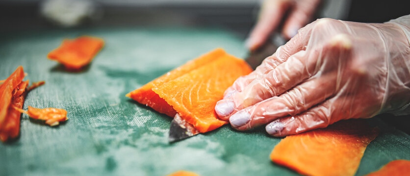 Close-up of hand sushi chef in gloves slices fresh salmon fish fillet at sushi bar.