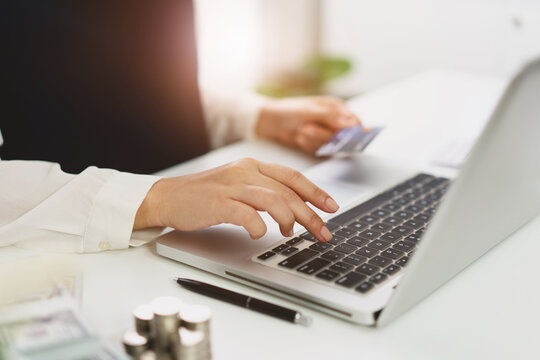 Woman spending money on Online shopping. Hands holding credit card and using laptop working at home e-commerce and internet banking concept