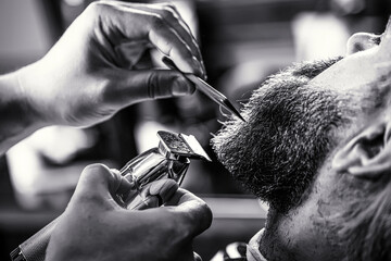 Barber works with a beard clipper. Hipster client getting haircut. Hands of a hairdresser with a beard clipper, closeup