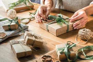 Fototapeta Christmas gift zero waste, eco friendly hand made box packaging gifts in kraft paper wooden table, eco christmas holiday concept, Christmas gift wrapping,eco decor banner obraz