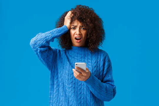 Indecisive troubled girl dont know what do, facing huge trouble. Shocked and cocnerned african-american woman in winter sweater grab head and grimace at camera, reading bad news on smartphone