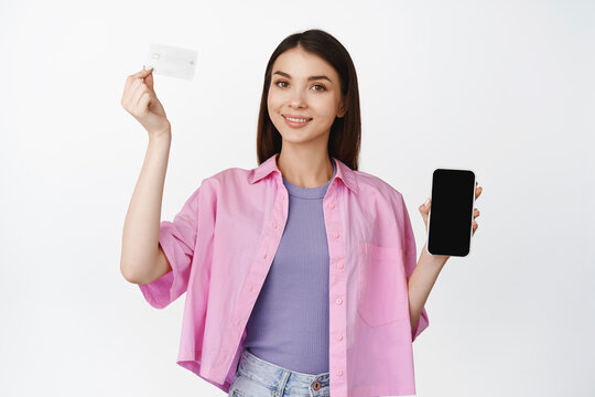Online shopping. Smiling brunette woman raising hand with credit card, showing smartphone screen, mobile interface, standing over whtie background