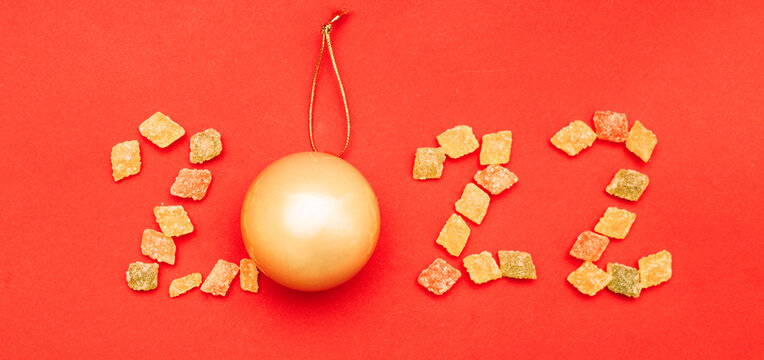 Numeral 2022 from multicolored sweets and golden christmas ball on red background