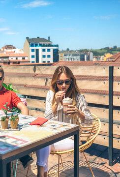 Elegant woman with sunglasses having a milkshake on a terrace