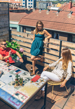 Top view of group of friends talking and drinking on a terrace